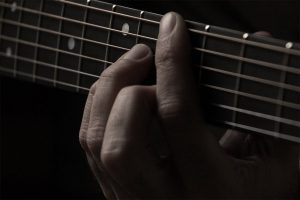 A man pressing the guitar chord