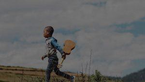 A kid holding ukulele running