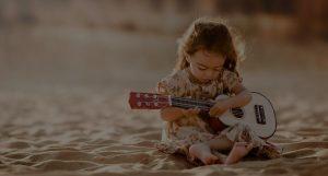 Girl playing Ukulele on the sands